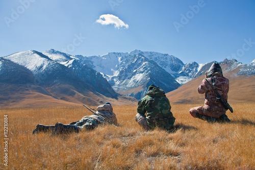 Obraz na plátne Three hunters looking through binoculars in mountains of Tien Sh