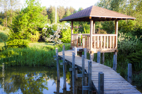 Cuadros en Lienzo Peaceful bower above a small pond in a summer garden