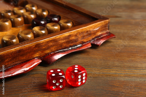 old backgammon with dice closeup on brown wooden background Fototapeta