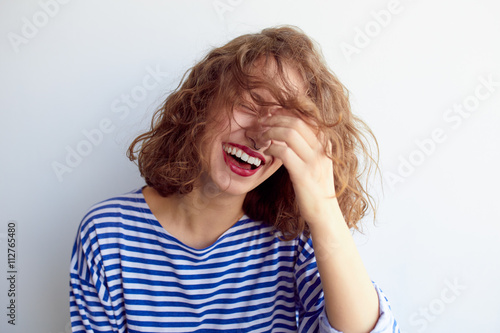 Fototapeta Laughing woman with curly hair on white wall