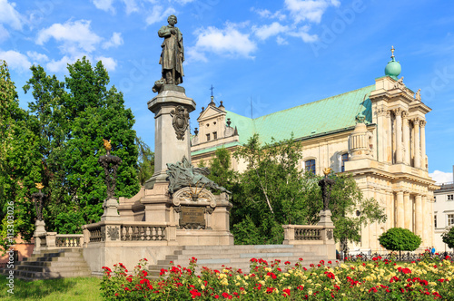 Fototapeta premium Warszawa, pomnik Adama Mickiewicza na Krakowskim Przedmieściu. W tle Kościół Wizytek - styl barokowy