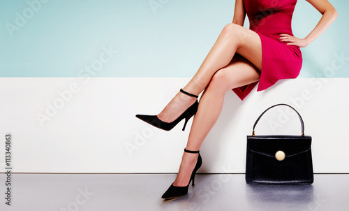 Fotografiet Beautiful legs woman wearing red dress with a black purse hand bag with high heels shoes sitting on the white bench