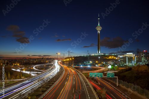 Highways of Tehran Filled with Passing Cars in Front of Milad Tower against Blue Sky with Clouds