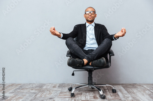 Canvas Print Relaxed african young man sitting and meditating on office chair