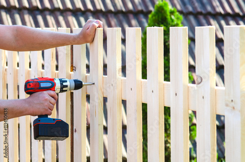 building a wooden fence with a drill and screw. Close up of his Fototapet