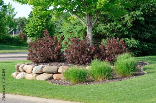 Fotografering Landscaping with Weigela Shrubs and Rock Retaining Wall