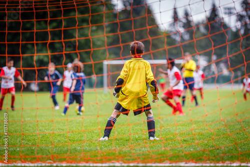 Fotografía Young soccer goalie defending the net in the rain