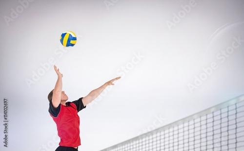Fototapeta Composite image of sportsman hitting volleyball