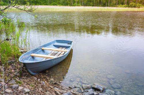 Fotografia Small rowboat lays on coast of still lake