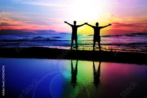 Canvas Print Gay couple admiring a rainbow sunset.