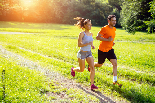 Canvas Print Athletic couple jogging in nature