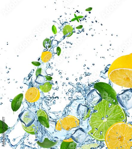 Fresh limes and lemons in water splash.