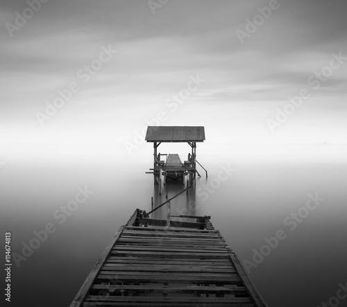Naklejki na drzwi Opuszczone molo na plaży w czerni i bieli