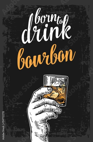 Slika na platnu Male hand holding a glass with bourbon and ice cubes