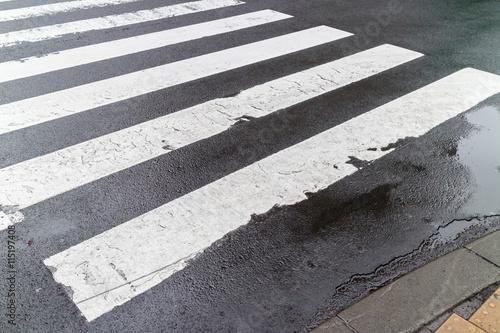 The wet pedestrian crosswalk on city street, safety concept. Fototapeta