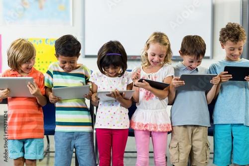 Carta da parati Smiling schoolchildren using digital tablet