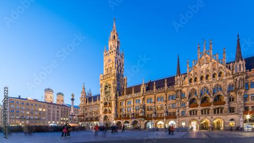 Fototapeta premium Marienplatz, Monachium Miasto Piękny panoramiczny widok na panoramę miasta Pejzaż Munchen nocą oświetlona architektura pod bezchmurnym niebem: Nowy Ratusz i Kościół Frauenkirche nocą, Bawaria, Niemcy.