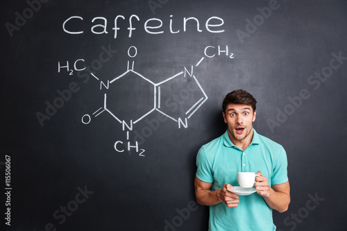 Fotomural Surprised student drinking coffee over drawn structure of caffeine molecule