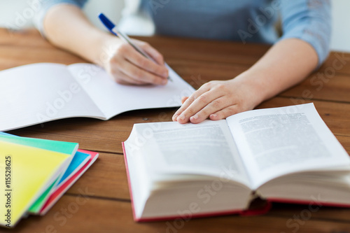 Photo close up of student with book and notebook at home