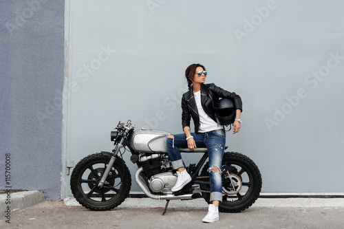 Canvas Print Biker woman in leather jacket on motorcycle
