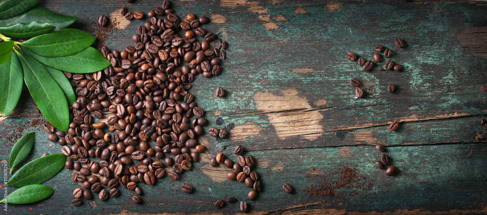 Roasted coffee beans with green leaves on a vintage background, top view with copy space