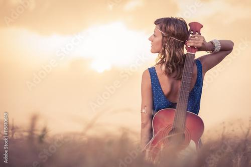 Obraz na plátně Mladý retro hippie stylu žena představuje a držení akustickou kytaru na zádech v pšeničném poli na západ slunce