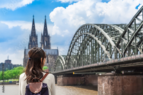View to Cologne / Young woman seen from back looking to rhine river, huge bridge and famous cathedral of Cologne, Germany