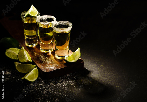 Fotografia Mexican Gold Tequila with lime and salt on wooden table, selective focus