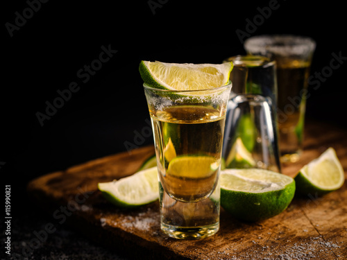 Obraz na płótnie Mexican Gold Tequila with lime and salt on wooden table, Shallow depth of field