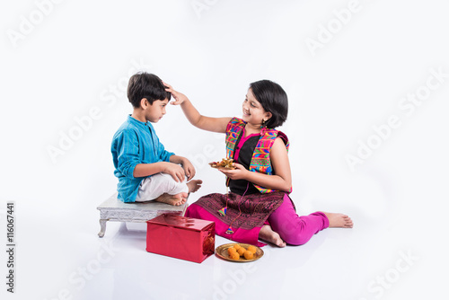 Pooja ceremony performed by cute looking sister and small brother on rakhi festival in India
