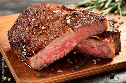 Medium Rare Ribeye steak on wooden board, selected focus