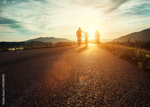 Ð¡yclists family traveling on the road at sunset