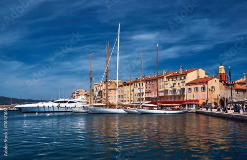 Obraz na plátně Sailboats and yachts moored to the quay port of Saint-Tropez, France