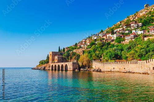 Fototapeta premium Krajobraz dawnej stoczni w pobliżu wieży Kizil Kule na półwyspie Alanya, dystrykt Antalya, Turcja, Azja. Znana miejscowość turystyczna z wysokimi górami. Część starożytnego starego zamku.