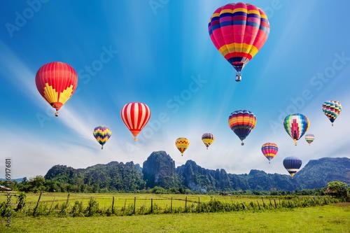 Vászonkép Colourful hot-air balloons flying over the mountain.