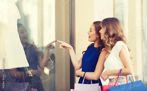 Obraz na płótnie happy women with shopping bags at shop window