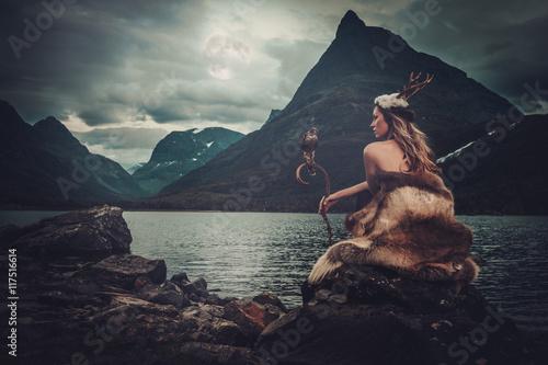 Fotografie, Obraz Nordic goddess in ritual garment with hawk near wild mountain lake in Innerdalen valley