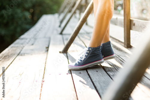 Obraz na płótnie Young woman standing on a bridge in jeans sneakers