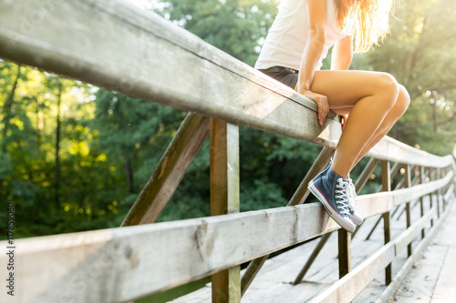 Canvas Print Young woman sitting on a bridge railing in jeans sneakers