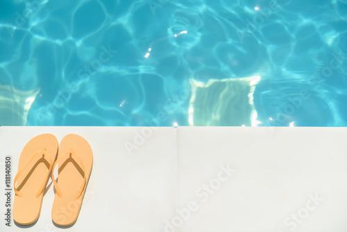 Fotografia Flip flop shoes near blue water