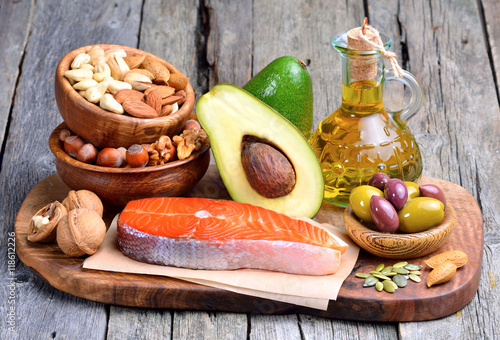 Selection of healthy fat sources on wooden background.
