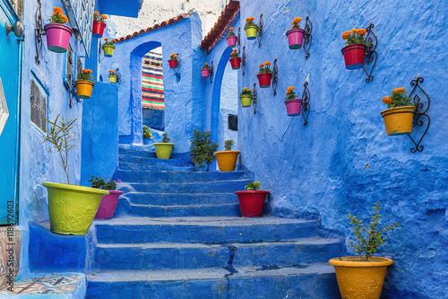 Niebieskie schody i ściany ozdobione kolorowymi doniczkami, medina Chefchaouen w Maroku.