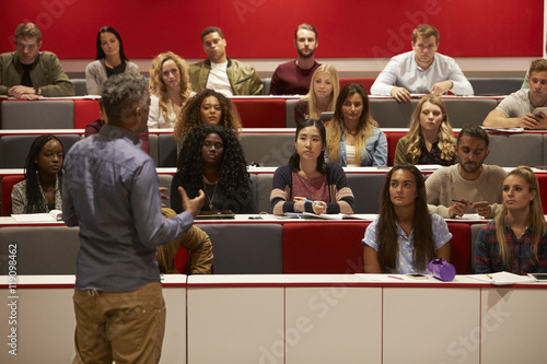Back view of man presenting to students at a lecture theatre Fototapeta
