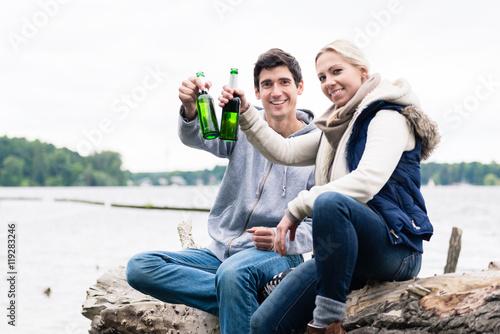 Fotografía couple sitting on tree stump at the riverside drinking beer