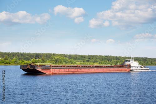 Fotografija River tugboat moves cargo barge on the Volga river in the summer navigation