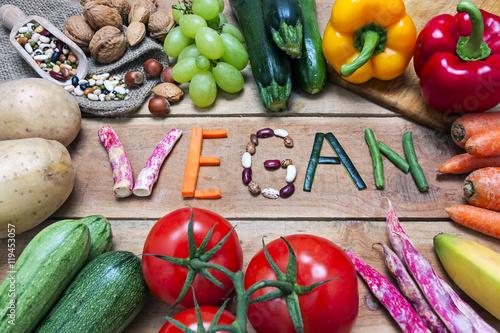 Fotografia vegan word on wood background and vegetable - food