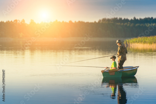 Fotografiet father and son catch fish from a boat at sunset
