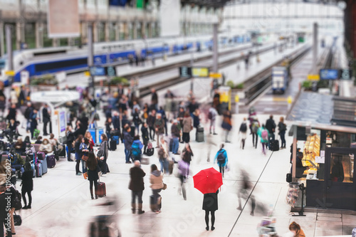 Obraz na płótnie woman with red umbrella waiting at train station and blurred people in motion, s