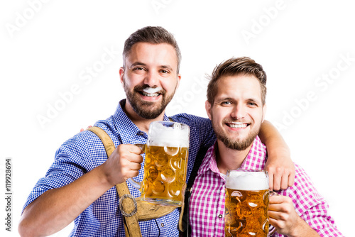 Carta da parati Men in traditional bavarian clothes holding mugs of beer