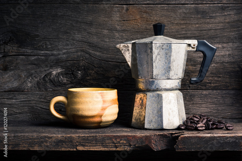 Leinwand Poster still life photography : old espresso maker with coffee beans and brown coffee c